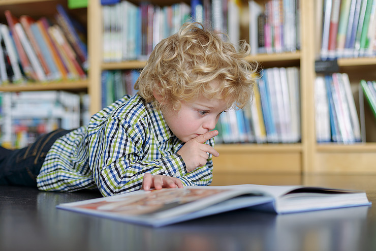 Close up of little blond curly haired boy lying on a floor in a library and reading a book.
